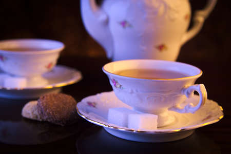 oldstyle: Old-style porcelain kettle with two cups of tea on black background with cookies retro style
