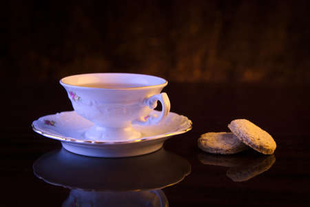 oldstyle: Old-style porcelain cup of tea on black background with cookies retro style Stock Photo
