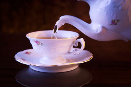 oldstyle: Old-style porcelain pouring tea from jug to cup of tea on black background retro