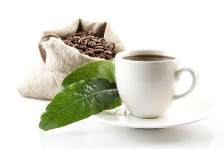 judia verde: La bolsa llena de granos de café con hojas verdes y la taza de café en blanco Foto de archivo