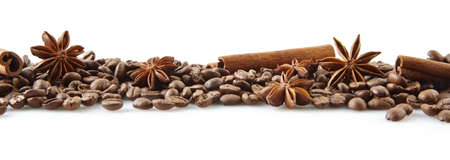 Closeup scattered coffee beans in line horizontal with anises and cinnamon sticks on white background Foto de archivo