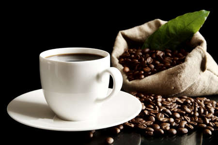 epicure: Cup of coffee with bag with coffee beans with green lead isolated on black