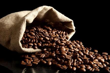overturned: Overturned sack full of coffee beans isolated on black