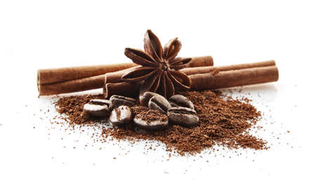 Closeup collected coffee beans with coffee powder with anise and cinnamon on white background