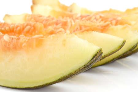 thou: Macro closeup shot of slice yellow canary melon on white background
