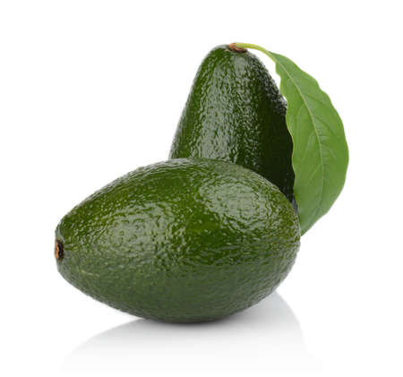 the stands: Avocado with leaf stands upright vertically with whole avocado lying on the table isolated on white background