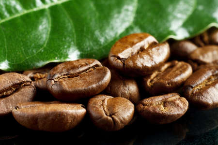 strewed: Macro closeup shot of coffee beans with green leaf on black background