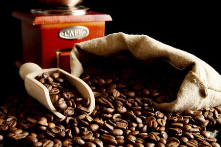winnower: Overturned sack full of coffee beans isolated on black with spatula and winnower