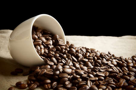 coffee spill: Strewn beans of coffee from a cup on black and flax material