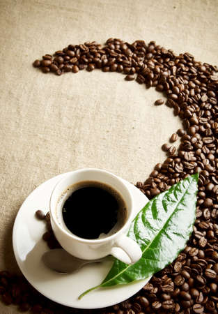 Scattered coffee beans twisted in a swirl with cup on fabric linen with green leaf Reklamní fotografie