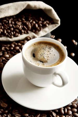 desayuno romantico: Macro studio shot of frothy black coffee, plenty of coffee beans view at breakfast on black background