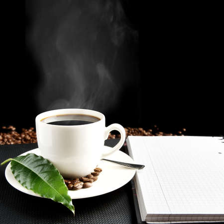 predilection: Cup of black coffee with mist with notebook, green coffee leaf, coffee beans at breakfast on black background