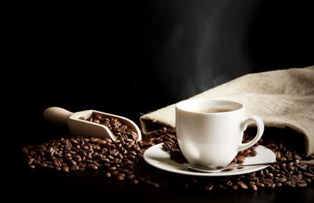 Cup of coffee with bag with coffee beans isolated on black desk