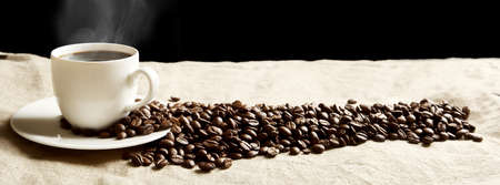 Closeup scattered coffee cup with foam and plenty beans in panoramic view on fabric linen Stock Photo