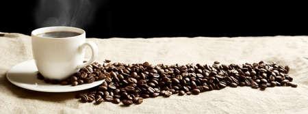 granos de cafe: Primer taza de café sembrado de granos de la espuma y la abundancia en vista panorámica sobre tela de lino