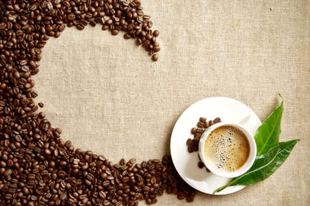 green: Scattered coffee beans twisted in a swirl with coffee cup with foam on fabric linen with green leaf Stock Photo