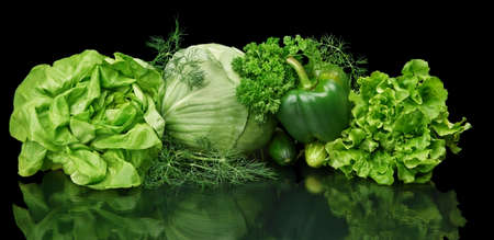 purifying: Collection of green vege-cabbage,lettuce,bell pepper,dill and parsley leaves on black background