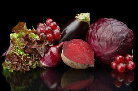Group of purple vegetables and fruits on black background