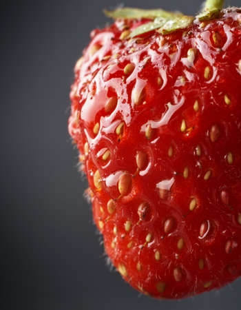 dewed: Cropped macro view of whole strawberry with drops of water on dark grey background Stock Photo