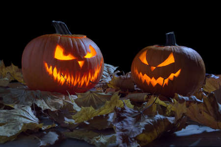 scary face: Creepy two pumpkins as jack o lantern among dried leaves on black background