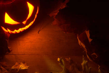 nightmarish: Scary halloween night with spooky evil face of jack o lantern in the corner with red shadows on the wooden surface
