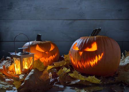 Scary jack o lantern pumpkins on wooden fence