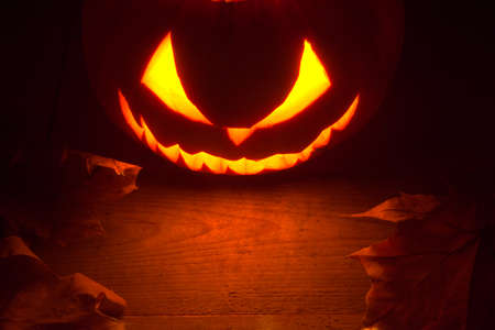 Scary halloween night with spooky evil face of jack o lantern at the top with red shadows on the wooden surface Stock Photo