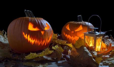 nightmarish: Spooky jack o lantern among dried leaves on black background