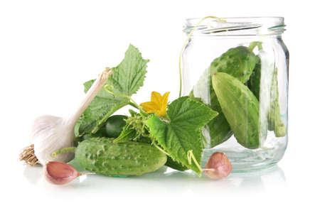 preserves: Ingredients for pickling or preserves cucumbers with flower bud,leaves,jar,garlic,dill flowers and tendrils isolated on white background