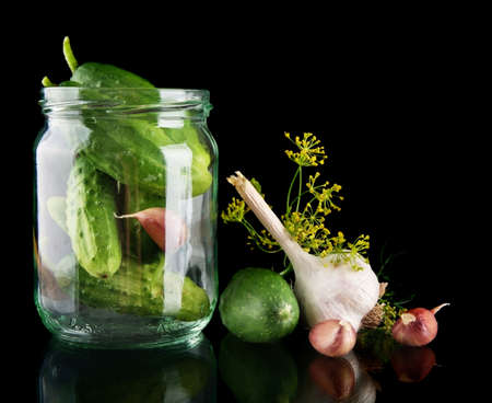 tendrils: Cucumbers in jar preparate for pickling with flower bud leaves, jar, garlic, dill flowers and tendrils isolated on black background Stock Photo