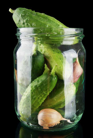 tendrils: Cucumbers in jar preparate for pickling with leaves,jar,garlic,dill and tendrils isolated on black background