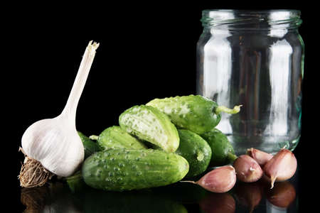 gherkins: Gherkins in jar preparate for pickling with flower bud,leaves,jar,garlic,dill flowers and tendrils isolated on black background