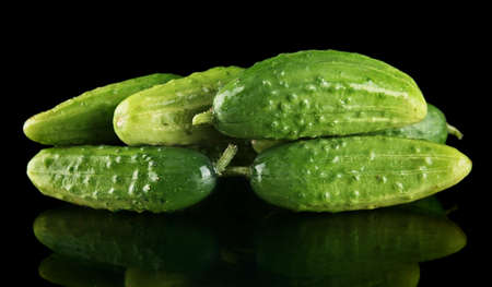 gherkins: Many fresh raw gherkins isolated on black background