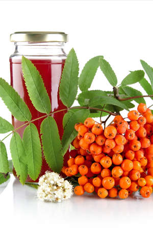 bunchy: Orange rowanberry with blossom, green leaves and jar of juice of rowanberry isolated on white background