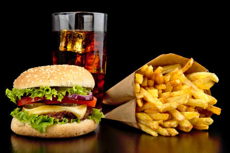 cheeseburger with fries: Big single cheeseburger with glass of cola and french fries on black wooden desk
