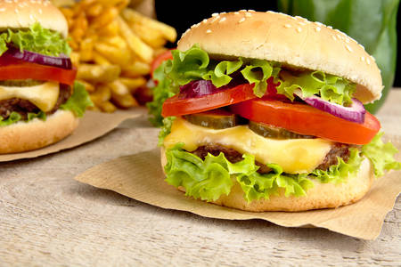 cheeseburgers: Big single cheeseburgers with french fries on wooden plank
