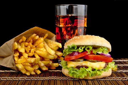 fast foods: Big single cheeseburger with french fries with glass of cola on wooden mat on black background
