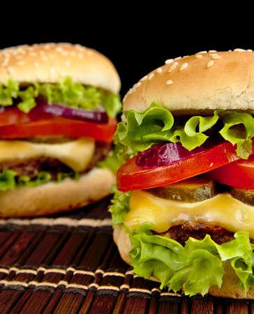 cheeseburgers: Big single cheeseburgers on wooden brown mat on black background