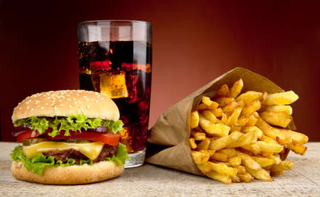 Cheeseburger with glass of cola and french fries on red spotlight background