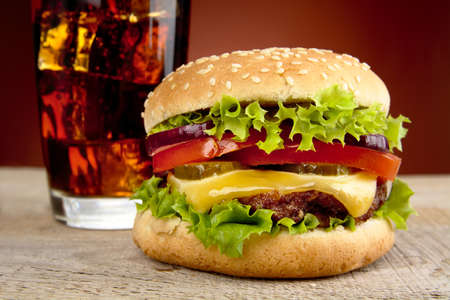 Cropped big single cheeseburger,glass of cola on wooden desk on red background Stock Photo