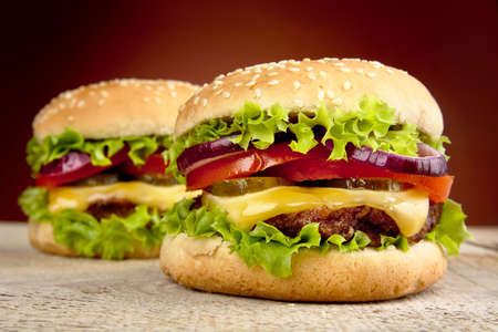 cheeseburgers: Two cheeseburgers on burned background