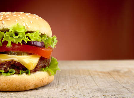 cropped: Cropped big single cheeseburger on red background
