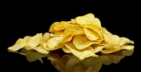 spicey: Many potato chips on black background