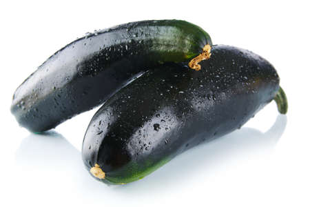 Black wet two courgettes on white background Stock Photo
