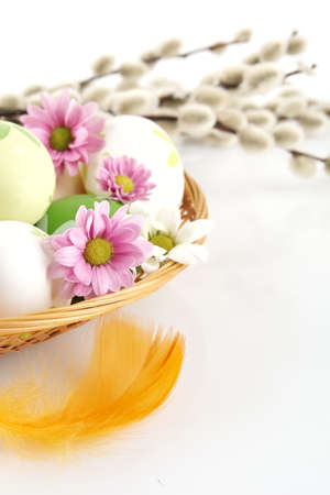 cropped shots: Cutted shot of pastel three colored easter eggs in the basket with pink flowers with catkins in the background on white Stock Photo