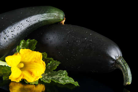 outspreading: Cropped view of two courgettes with flowers on black background