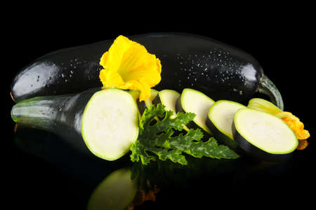 outspreading: Mature wet courgettes cut into slices with flower and courgette leaf on black background