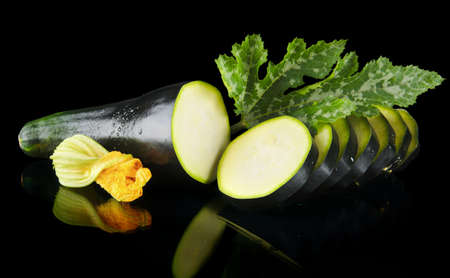 dewed: Mature dewed zucchini cut into slices with flower and courgette leaf on black background