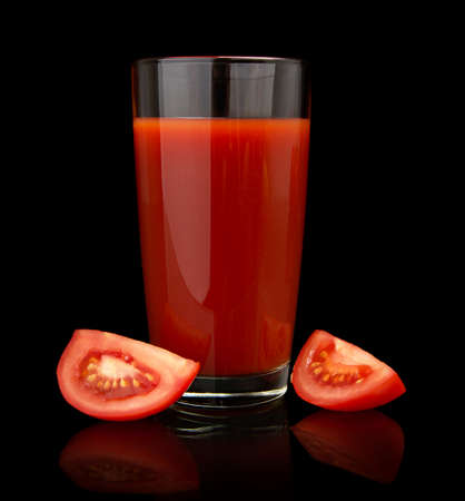 quarters: Glass of tomato juice with quarters of tomatoes isolated on black background Stock Photo