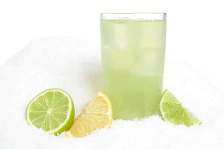 citrons: Glass of lime juice with ice cubes,limes and lemons halves on snow on white background Stock Photo